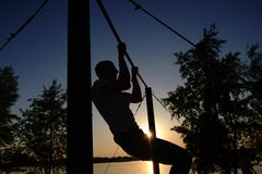 Young man doing pull ups on horizontal bar outdoors during sunset - fitness, sport, exercising, training and lifestyle royalty free stock photography