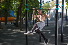 Young man doing pull ups on horizontal bar outdoors, workout, sp Royalty Free Stock Image
