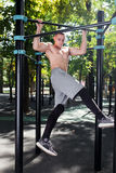 Young man doing pull ups on horizontal bar outdoors, workout, sp Stock Photo