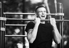 Young man doing pull ups on horizontal bar outdoors, workout, sport concept Royalty Free Stock Images