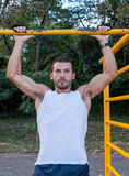 Young Man Doing Pull Ups. Young Man Working Out Outdoors Doing Pull Ups Stock Photos