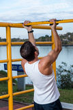 Young Man Doing Pull Ups. Young Man Working Out Outdoors Doing Pull Ups Stock Photo
