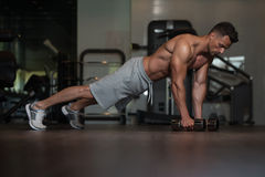 Young Man Doing Push Ups With Dumbbells On Floor Stock Photo