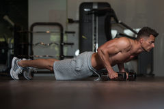 Young Man Doing Push Ups With Dumbbells On Floor Royalty Free Stock Photography