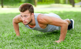 Young man doing push ups on grass in summer park Royalty Free Stock Image