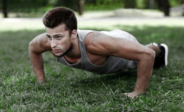 Young man doing push ups on grass in summer park Stock Photography