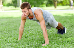 Young man doing push ups on grass in summer park Royalty Free Stock Photography