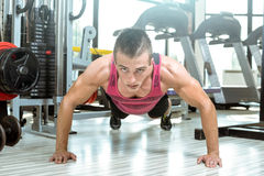 Young man doing push-ups in gym Royalty Free Stock Images