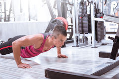 Young man doing push-ups in gym. Young adult man doing push ups in gym Royalty Free Stock Photos
