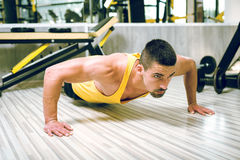 Young man doing push-ups in gym Royalty Free Stock Photography