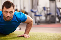 Young man doing push ups at a gym, looking to camera, copy space Royalty Free Stock Image