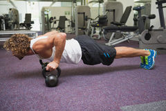 Young man doing push ups with kettle bells in gym Stock Photo