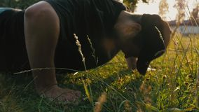 Young man doing push-ups on the lawn in a natural public park. Young man doing push ups on the lawn in a natural public park. Sunset time stock footage