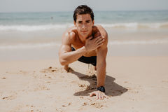 Young man doing push-ups on the ocean beach. Sports and healthy lifestyle. Young man doing push-ups on the ocean beach Stock Photos