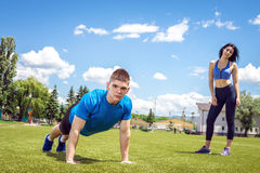 Young man doing push ups outdoor in grass. Stock Photos
