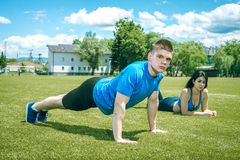 Young man doing push ups outdoor in grass. Stock Photo