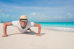 Young man doing push ups on perfect beach Royalty Free Stock Image