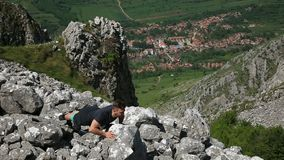 Man Doing Push-ups on Rocks. Young man doing push-ups on rocks in mountains stock video footage