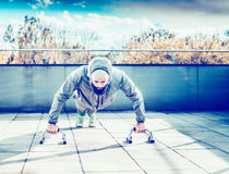 Young man doing push-ups on the terrace of the house, on the background of  spring landscape of the city Stock Photography