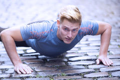 Young man doing pushups on cobblestone Stock Image
