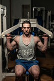 Young man doing shoulder press on machine Stock Photo