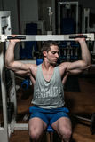 Young man doing shoulder press on machine. Young bodybuilder doing shoulder press on machine in gym royalty free stock images