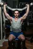 Young man doing shoulder press on machine in gym Royalty Free Stock Photography
