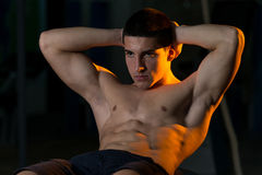 Young Man Doing Sit-Ups With Exercise Ball. Exercising Abdominals On Fitness Ball Stock Photo