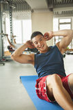 Young man doing sit-ups in the gym Stock Photos