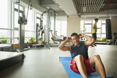 Young man doing sit-ups in the gym Stock Image