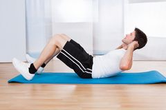 Young man doing sit-ups Stock Images