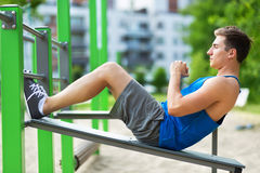 Young man doing sit-ups at outdoor gym Royalty Free Stock Photos