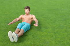 Young man doing sit-ups on sports field. Young man training outdoors and doing sit-ups on green sports field royalty free stock images