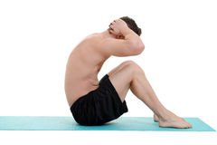 Young man doing situps on blue mat Royalty Free Stock Image