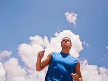 Young Man Doing Sports Runner Jogging Blue Sky. Young people doing sport activities, man runner jogging against blue sky. Copy space. Concept of leisure, health Royalty Free Stock Images