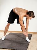 Young man doing standing leg stretches Royalty Free Stock Images