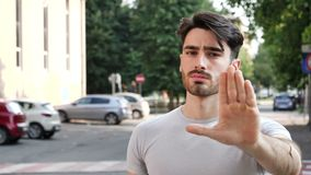 Young man doing stop sign with his hand stock footage