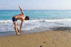 Young man doing streching fitness  training at the beach Royalty Free Stock Images