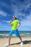 Young man doing stretching exercises on beach Royalty Free Stock Images