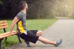 Young man doing stretching exercises on a bench Royalty Free Stock Photos