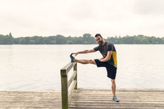 Young man doing stretching exercises on a deck Royalty Free Stock Image