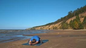 Young man doing thoracic stretching on a beach at sunset light stock video