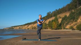 Young man doing thoracic stretching on a beach at sunset light stock footage