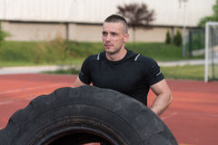 Young Man Doing Tire Flip Workout Outdoor Stock Photography