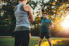 Young man doing weight training with trainer Stock Photos