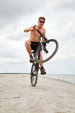 Young man doing wheelie Stock Photography