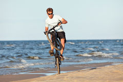 Young man doing wheelie. With bicycle in beach Stock Photos