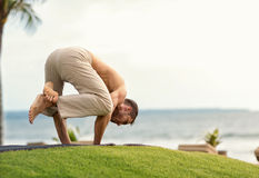 Young man doing yoga on the beach Stock Photo