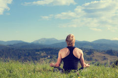 Young man doing yoga exercise. At the summer meadow stock photo