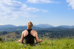 Young man doing yoga exercise. At the summer meadow royalty free stock image